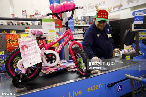 An employee prepares to scan a children's bicycle for a customer at a WalMart Stores Inc location in Burbank California US on Thursday Nov 16 2017...