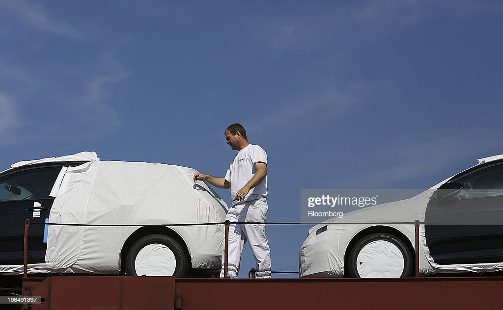 An employee prepares to unload new Volkswagen AG automobiles from a rail wagon at the port of Koper, operated by Luka Koper d.d., in Koper, Slovenia, on Thursday, May 9, 2013. The former Yugoslav nation, mired in its second recession since 2009, will contract this year and next, according to a May 3 report by the European Commission. Photographer: Chris Ratcliffe/Bloomberg via Getty Images