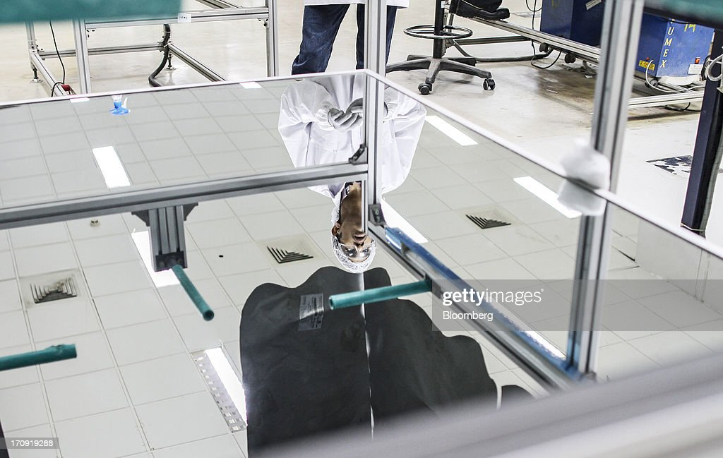 An employee preparing an inspection chamber is reflected in the chamber's work bench on the solar photovoltaic module production line at the Tata Power Solar Systems Ltd. manufacturing plant in Bangalore, India, on Tuesday, June 11, 2013. Tata Groups solar unit is expanding its business building plants for customers, forecasting that offices and factories will be paying more for grid power than solar by 2016 in most Indian states. Photographer: Dhiraj Singh/Bloomberg via Getty Images