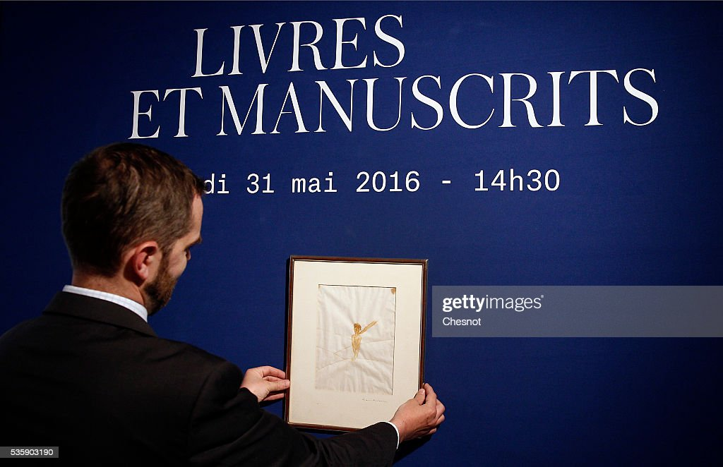 An employee presents a drawing from Antoine de Saint-Exupery that will be sold tomorrow by the auction house Artcurial on May 30, 2016 in Paris, France.