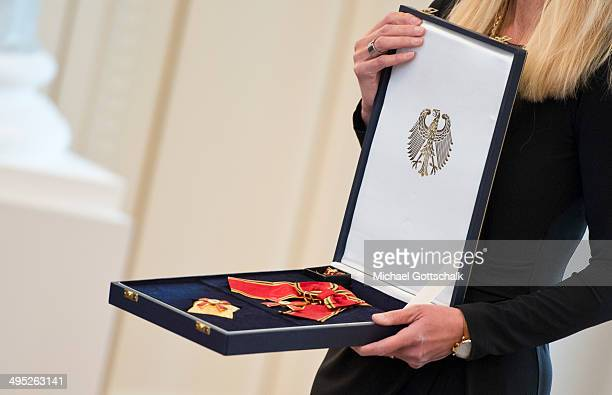 An employee presents a Federal Cross of Merit during the swearingin of Doris Koenig as new judge at German Federal Constitutional Court on June 02...