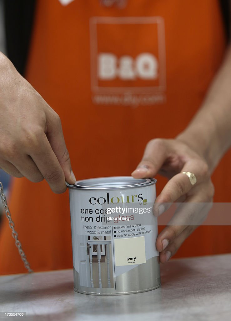 An employee pries the lid off a tin of paint inside a B&Q home improvement store, operated by Kingfisher Plc, in London, U.K., on Tuesday, July 16, 2013. Financial assistance for first-time home buyers in Britain is likely to prompt a resurgence of do-it-yourself spending after several years of decline, according to Kingfisher Plc Chief Executive Officer Ian Cheshire. Photographer: Chris Ratcliffe/Bloomberg via Getty Images