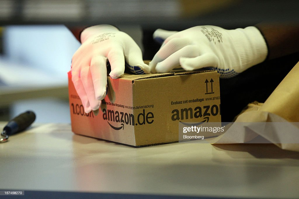 An employee processes a customer's order at the Amazon.co.uk Marston Gate 'Fulfillment Center,' the U.K. site of Amazon.com Inc. in Ridgmont, U.K., on Monday, Dec. 3, 2012. U.K. consumer confidence unexpectedly increased to an 18-month high in November as Britons become more optimistic about the economy and their finances, GfK NOP Ltd. said. Photographer: Simon Dawson/Bloomberg via Getty Images
