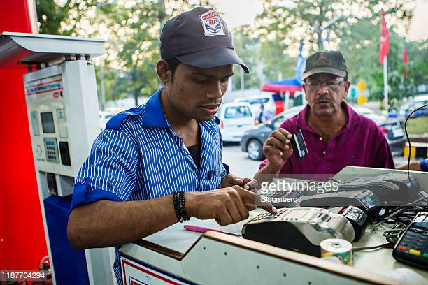 An employee processes a customer's payment at a Hindustan Petroleum Corp gas station in New Delhi India on Monday Nov 11 2013 Hindustan Petroleum is...