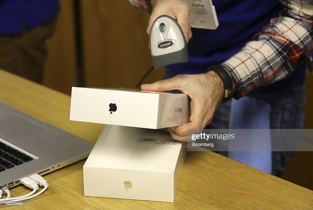 An employee processes a customer's purchase of Apple Inc. iPad minis at the company's Covent Garden store in London, U.K., on Friday, Nov. 2, 2012. Apple Inc.'s iPad mini tablet goes on sale in the U.K. today. Photographer: Simon Dawson/Bloomberg via Getty Images