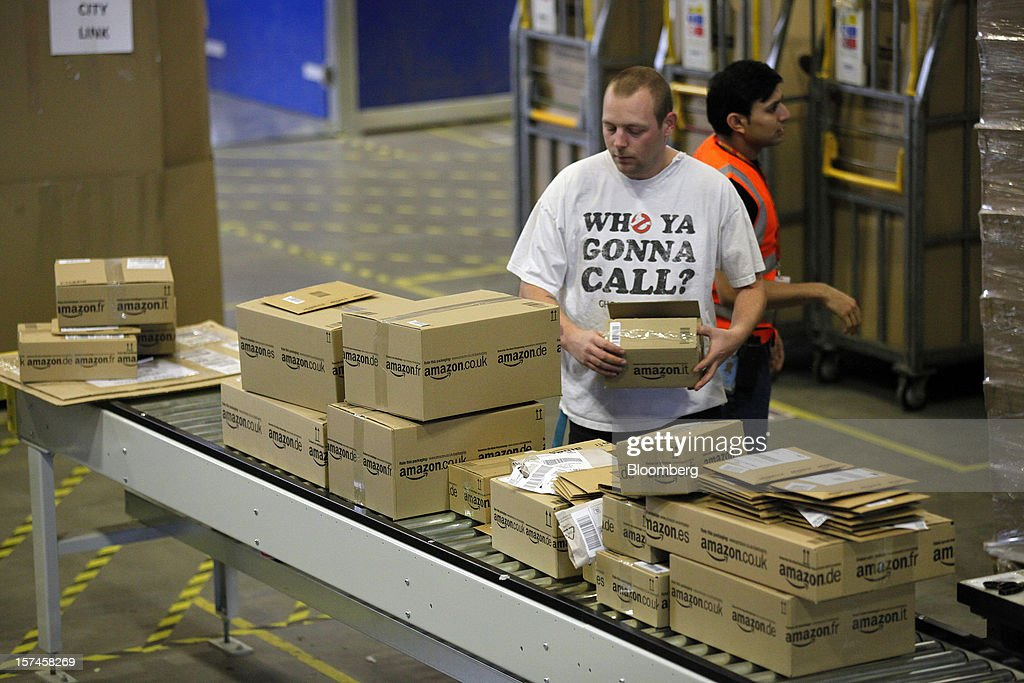 An employee processes customer orders at the Amazon.co.uk Marston Gate 'Fulfillment Center' the U.K. site of Amazon.com Inc. in Ridgmont, U.K., on Monday, Dec. 3, 2012. U.K. consumer confidence unexpectedly increased to an 18-month high in November as Britons become more optimistic about the economy and their finances, GfK NOP Ltd. said. Photographer: Simon Dawson/Bloomberg via Getty Images