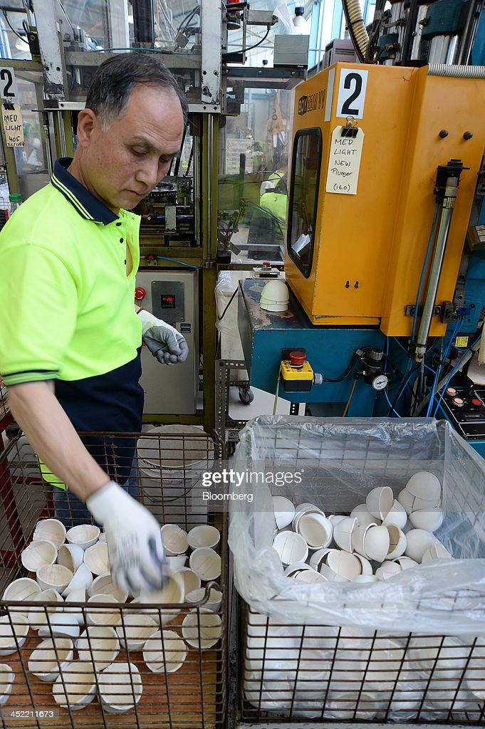 An employee processes leather casings for white cricket balls in a molding machine at the Kookaburra Sports Pty Ltd. plant in Melbourne, Australia, on Tuesday, Nov. 26, 2013. Australian businesses need to boost efficiency to maintain growth in living standards, Reserve Bank of Australia Deputy Governor Philip Lowe said. Photographer: Carla Gottgens/Bloomberg via Getty Images