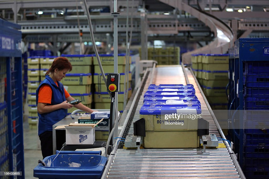 An employee processes letters beside a conveyor belt in the main hall at the Russian Post automated sorting center in Podolsk, Russia, on Wednesday, Nov. 14, 2012. Alexander Kiselev, Russian Post's chief executive officer, needs to invest 200 billion rubles through 2020 to turn around a company that described its infrastructure as 'the most expansive, but the least efficient' in a strategy plan this year. Photographer: Andrey Rudakov/Bloomberg via Getty Images