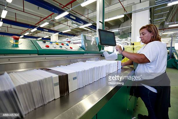 An employee processes mail through a machine inside a Poste Italiane SpA postal sorting office in Fiumicino near Rome Italy on Tuesday Sept 15 2015...