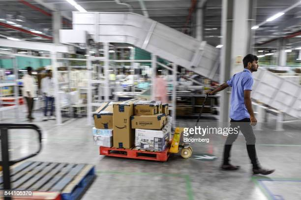An employee pulls a cart stacked with packages at the Amazoncom Inc fulfillment center in Hyderabad India on Thursday Sept 7 2017 Amazon opened its...