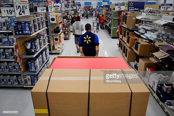 An employee pulls a forklift with display units for DVD movies at a WalMart Stores Inc location ahead of Black Friday in Los Angeles California US on...