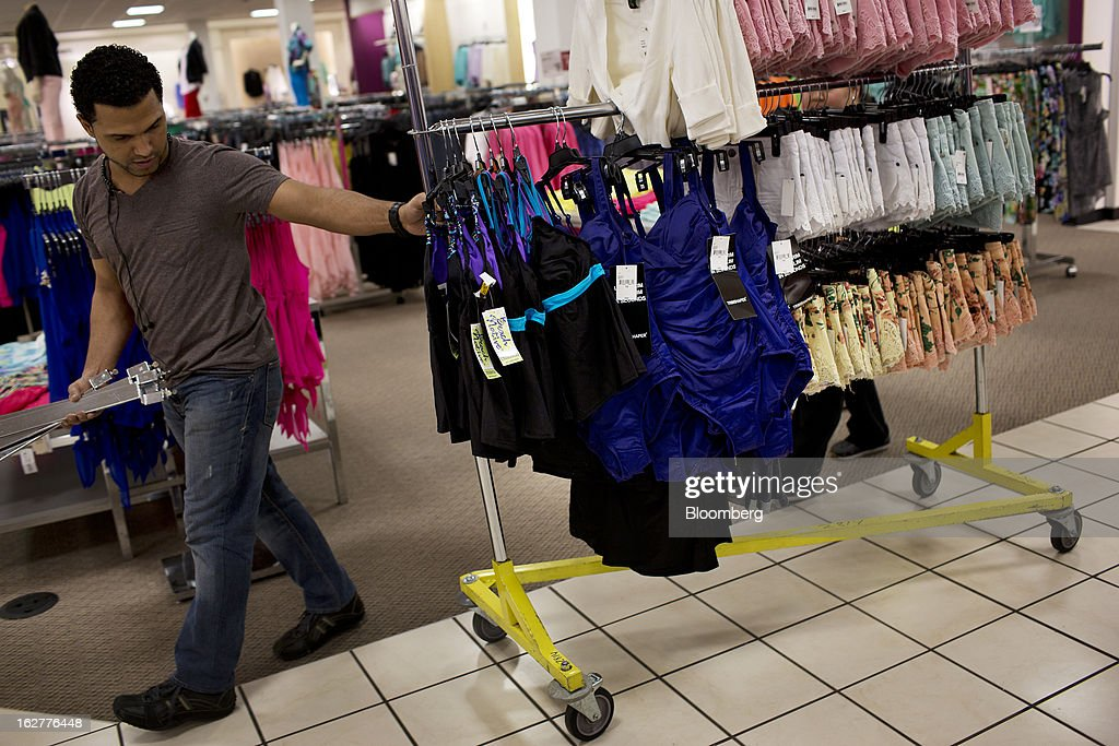 An employee pulls a rack of clothes at a J.C. Penney Co. store in the Queens borough of New York, U.S., on Tuesday, Feb. 26, 2013. Confidence among U.S. consumers jumped more than forecast in February as Americans adjusted to a higher payroll tax and signs of a recovering housing market spurred faith in the future. J.C. Penney Co. is scheduled to release earnings data on Feb. 27. Photographer: Victor J. Blue/Bloomberg via Getty Images