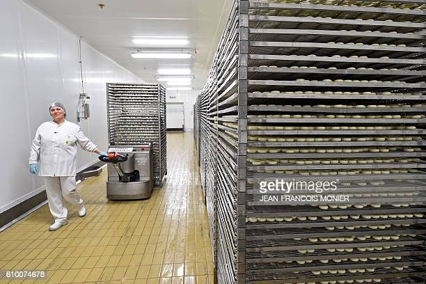 An employee pulls a tray cart of unwrapped Babybel cheese portions at the Bel Group cheese factory in Evron northwestern France on September 22 2016...