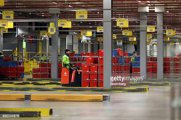 An employee pulls a trolley load of completed customer order crates at the Ocado Group Plc distribution centre in Dordon UK on Friday Dec 16 2016...