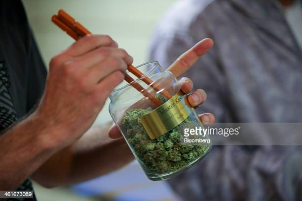 An employee pulls marijuana out of a large canister for a customer at the LoDo Wellness Center in downtown Denver Colorado US on Thursday Jan 9 2014...