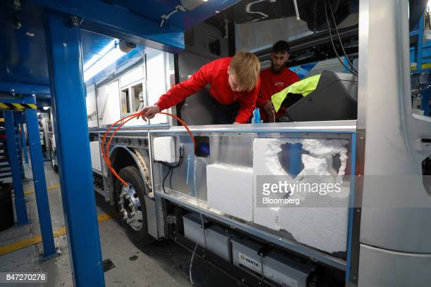 An employee pulls wires through a side panel of an Enviro 400 London bus at the Alexander Dennis Ltd factory in Scarborough UK on Wednesday Sept 13...