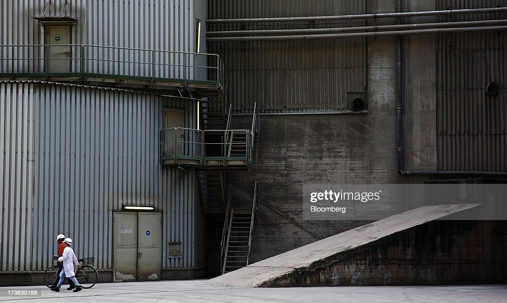 An employee pushes a bicycle as he walks with a colleague past warehouses at Holcim Ltd.'s cement plant in Untervaz, Switzerland, on Wednesday, July, 17, 2013. Holcim Chief Executive Officer Bernard Fontana has cut costs and expanded in emerging regions such as Latin America and Indonesia to counter a construction slump in Europe, caused by the region's economic crisis. Photographer: Gianluca Colla/Bloomberg via Getty Images