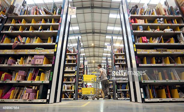 An employee pushes a cart between racks of books and merchandise as he processes customer orders ahead of shipping at one of Amazoncom Inc's...