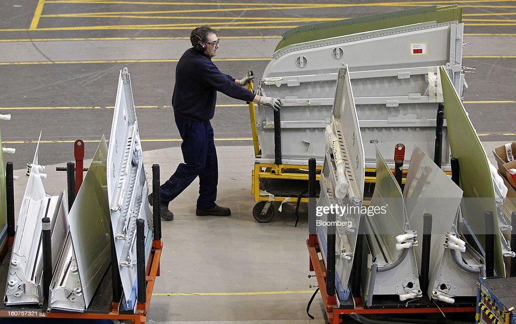 An employee pushes a cart loaded with wing sections of Airbus A320 single-aisle passenger aircraft during assembly at the company's factory in Broughton, U.K., on Monday, Feb. 4, 2013. Airbus SAS won a $9 billion order from Steven Udvar-Hazy's Air Lease Corp. that includes 25 A350 wide-body jets, a competitor to Boeing Co.'s grounded 787 Dreamliner. Photographer: Paul Thomas/Bloomberg via Getty Images