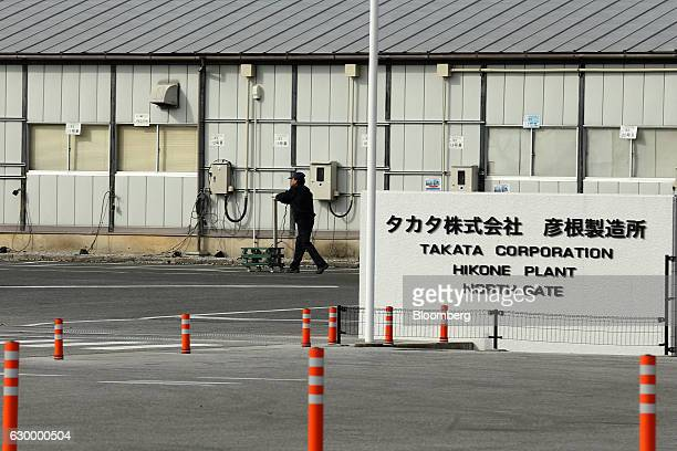An employee pushes a cart past a signage near the north gate entrance to Takata Corp's Hikone plant in Hikone Shiga Japan on Friday Nov 25 2016...