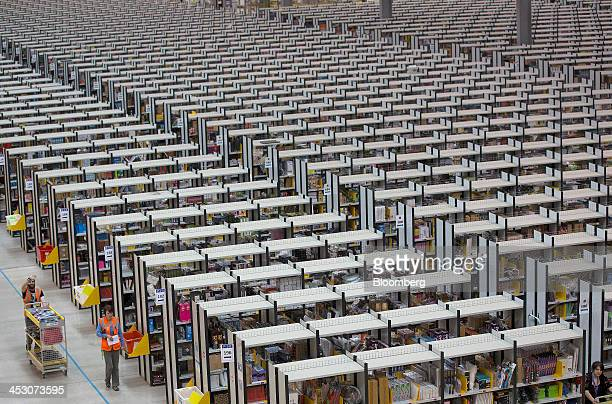 An employee pushes a cart past rows of storage aisles as he processes customer orders ahead of shipping at one of Amazoncom Inc's fulfillment centers...