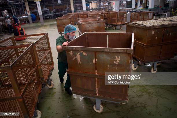 An employee pushes a container at the 'Agro Sevilla' olive manufacturing company in La Roda de Andalucia on September 29 2017 / AFP PHOTO / JORGE...