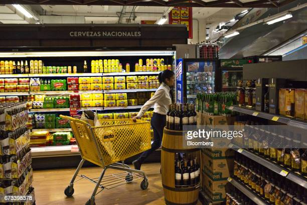 An employee pushes a shopping cart past the beer aisle at an Almacenes Exito SA store in Bogota Colombia on Thursday April 20 2017 The Foundation for...