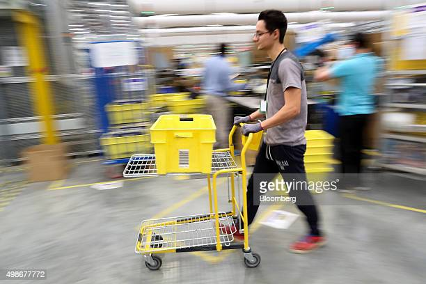 An employee pushes a trolley at the Amazoncom Inc fulfillment center in Hemel Hempstead UK on Wednesday Nov 25 2015 WalMart and Amazon's toy pricing...