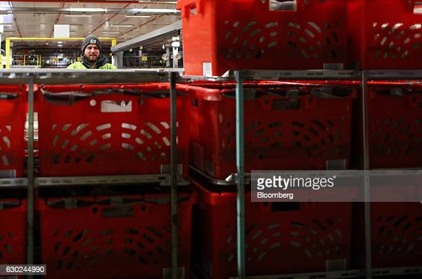 An employee pushes a trolley load of completed customer order crates on to a delivery vehicle at the Ocado Group Plc distribution centre in Dordon UK...