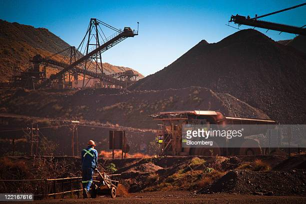 An employee pushes an equipment trolley through the pit at Sishen open cast mine operated by Kumba Iron Ore Ltd an iron oreproducing unit of Anglo...