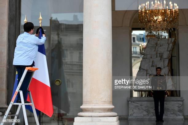 An employee puts a black ribbon on a French flag at the Elysee presidential Palace in Paris on May 24 2017 in tribute to the victims of the May 22...