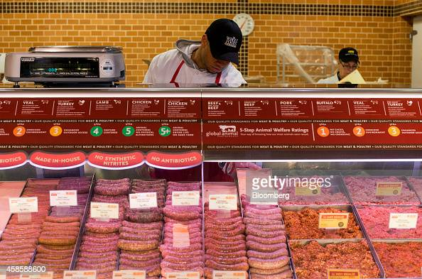 An employee puts a tray of sausages into the display counter at the meat department of a Whole Foods Market Inc store in Dublin Ohio US on Friday Nov...