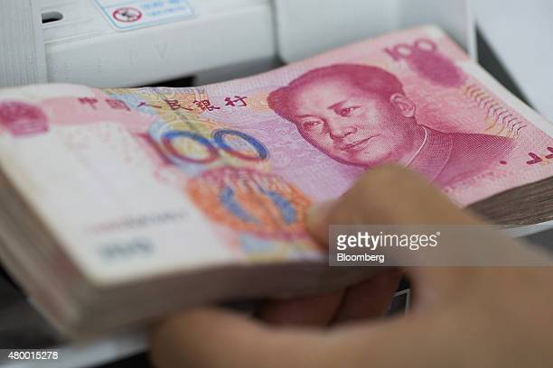 An employee puts Chinese onehundred yuan banknotes into a money counting machine at the Korea Exchange Bank headquarters in Seoul South Korea on...