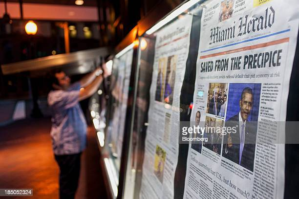 An employee puts front pages in the displays in front of the Newseum in Washington DC US on Thursday Oct 17 2013 The passage last night by wide...