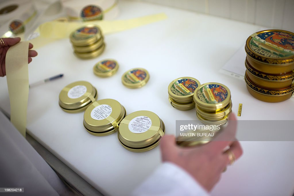 An employee puts labels on caviar boxes in the lab of Kaspia Caviar, on December 11, 2012 in Paris.