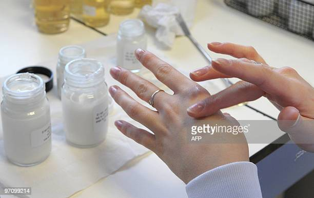 An employee puts on her skin a cosmetics product in a laboratory at Shiseido International France a subsidiary of Japan's top cosmetics maker...