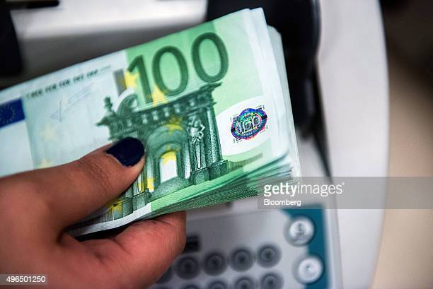 An employee puts onehundred euro currency banknotes into a money counting machine at a bank branch inside the FHB Commercial Bank Ltd also known as...