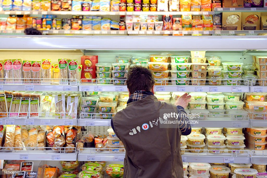 An employee puts out fresh ready-to-eat products on the shelves in a supermarket in Besançon, eastern France, on March 1, 2013.