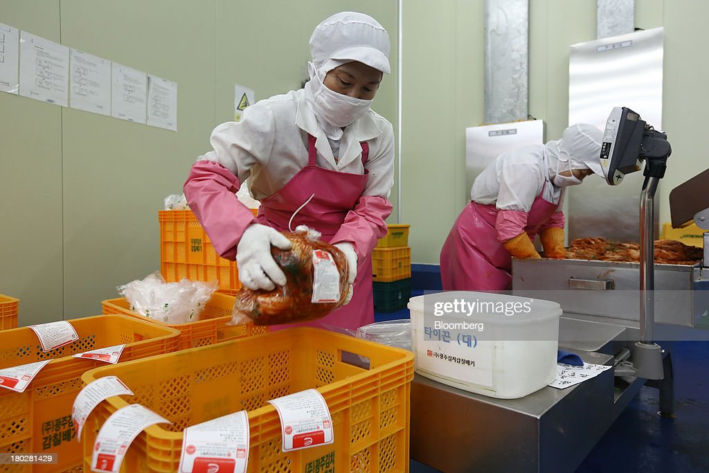 An employee puts packaged kimchi into a crate on the production line at the Gamchilbaegi Co. kimchi factory in Gwangju, South Korea, on Tuesday, Sept. 10, 2013. Gross domestic product rose 1.1 percent in the second quarter from the preceding three months, the most in more than two years, central bank data showed Sept. 5. Photographer: SeongJoon Cho/Bloomberg via Getty Images