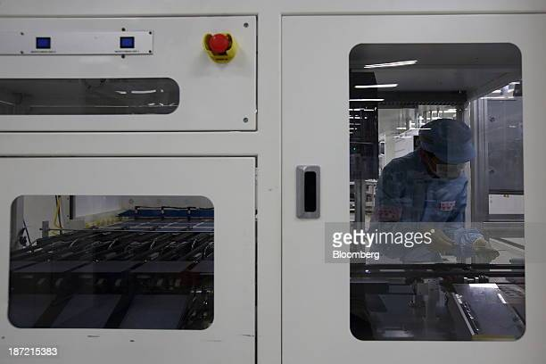 An employee puts solar cells into a machine on the production line at the Hyundai Heavy Industries Co solar factory in Eumseong South Korea on...