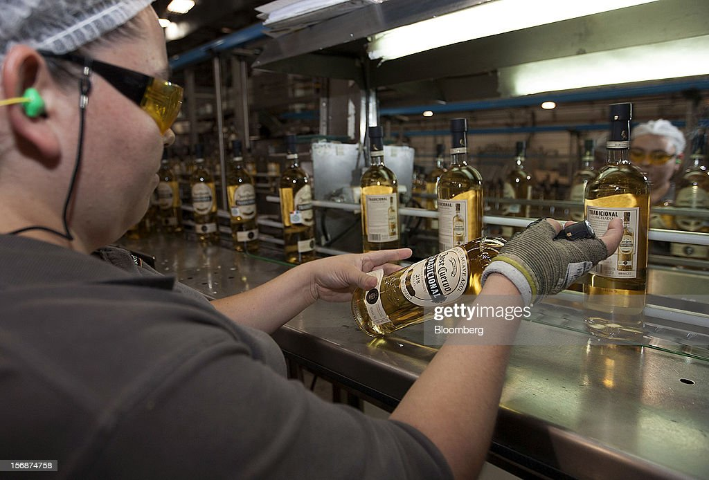 An employee puts the label on a bottle of Jose Cuervo Tradicional on the production line at the Tequila Cuervo La Rojena S.A. de C.V. bottling factory in Guadalajara, Mexico, on Thursday, Nov. 22 2012. There are more than 200 types of agave in Mexico, but use of the blue agave plant was made compulsory in the last century to the issuance of the Official Mexican Standard for Tequila production. Photographer: Susana Gonzalez/Bloomberg via Getty Images