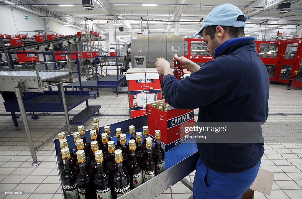 An employee quality control checks a box loaded with Campari bottles after production at Davide Campari-Milano SpA's factory in Novi Ligure, Italy, on Wednesday, Nov. 21, 2012. Business conditions in Italy, where Campari gets almost a third of annual revenue, are likely to remain volatile in the fourth quarter and early next year, Chief Executive Officer Bob Kunze-Concewitz said. Photographer: Alessia Pierdomenico/Bloomberg via Getty Images