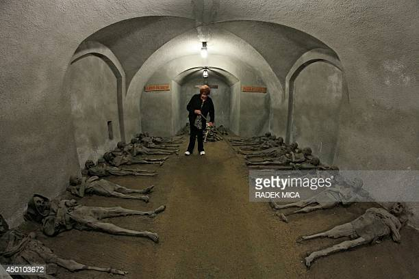 An employee rakes the earth between mummies in the tomb of the Capuchin monastery in Brno Czech Republic on June 5 2014 In the Capuchin Crypt monks...