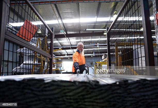 An employee reaches for a metal rod to be shaped on the production line at the Backwell IXL plant in Geelong Australia on Tuesday May 20 2014...