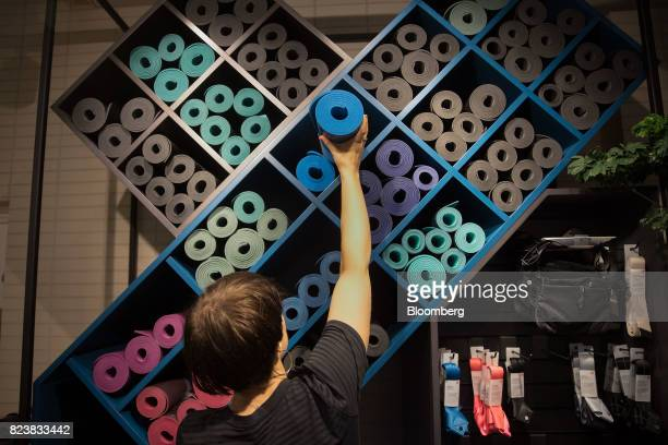 An employee reaches for a yoga mat at the Lululemon Athletica Inc sports apparel store on Regent Street in London UK on Thursday July 27 2017...