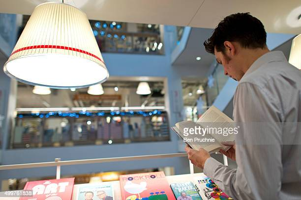 An employee reads a book in Foyles bookshop on December 3 2015 in London United Kingdom Foyles flagship store on Charing Cross Road was founded in...