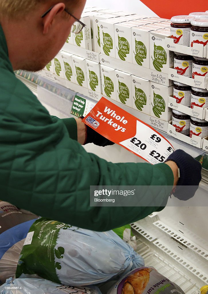 An employee rearranges a price tag above frozen turkeys on a freezer inside a Morrisons supermarket, operated by William Morrisons Supermarkets Plc, in Chadderton, U.K., on Monday, Dec. 17, 2012. The British Christmas is the biggest epicurean occasion of the year, with households spending a total of 4 billion pounds on food in the final week before Dec. 25. Photographer: Paul Thomas/Bloomberg via Getty Images