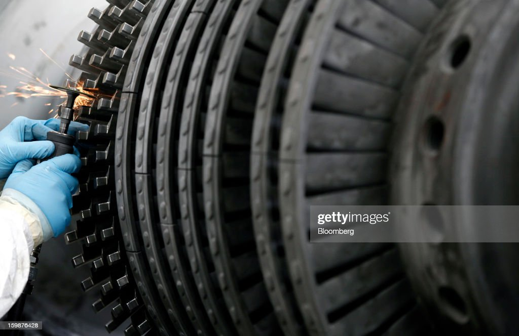 An employee refines the fixed components of a turbine rotor shaft during manufacture at Ansaldo Energia SpA's power-plant production facility in Genoa, Italy, on Friday, Jan. 18, 2013. Finmeccanica SpA is seeking binding bids for assets, including a majority stake in Ansaldo Energia, by Jan. 23, while a final decision will be made at a later board meeting, Ansa reported Jan. 16. Photographer: Alessia Pierdomenico/Bloomberg via Getty Images