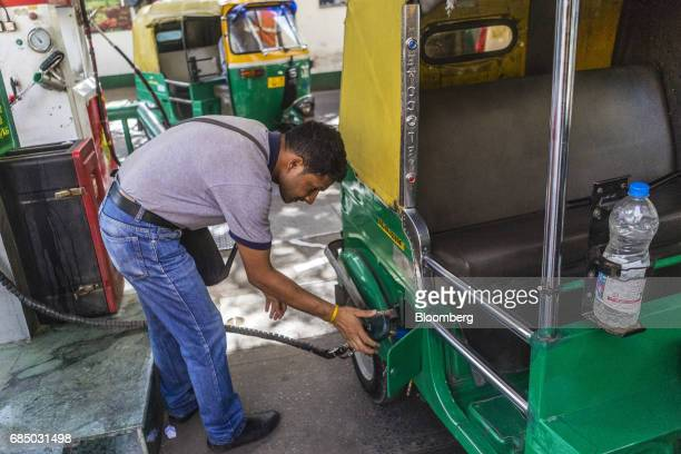 An employee refuels an auto rickshaw with compressed natural gas at an Indraprastha Gas Ltd gas station in New Delhi India on Wednesday May 17 2017...