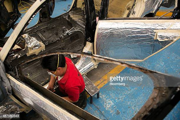 An employee reinforces the door of a sport utility vehicle at Ballistic Protection Co's armored car workshop in Mexico City Mexico on Tuesday April...